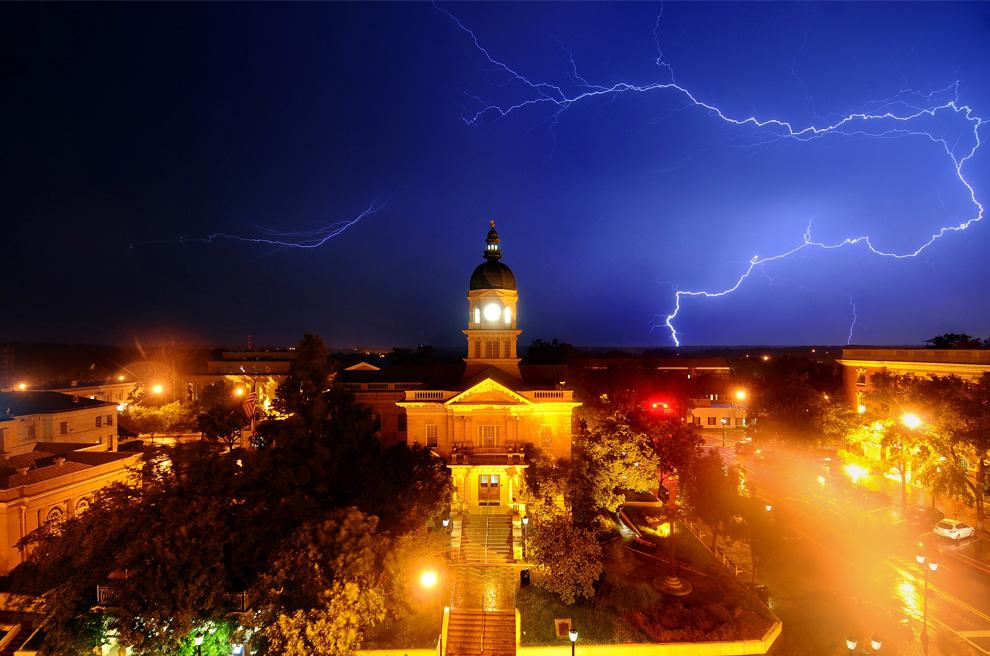 1) Молния освещает небо позади здания мэрии в городе Афины, штат Джорджия рано утром, 18 июня 2009. Более 4000 человек остались без света в Северо-Восточной Джорджии во время этой грозы. (AP Photo/The Athens Banner-Herald, Kelly Lambert)