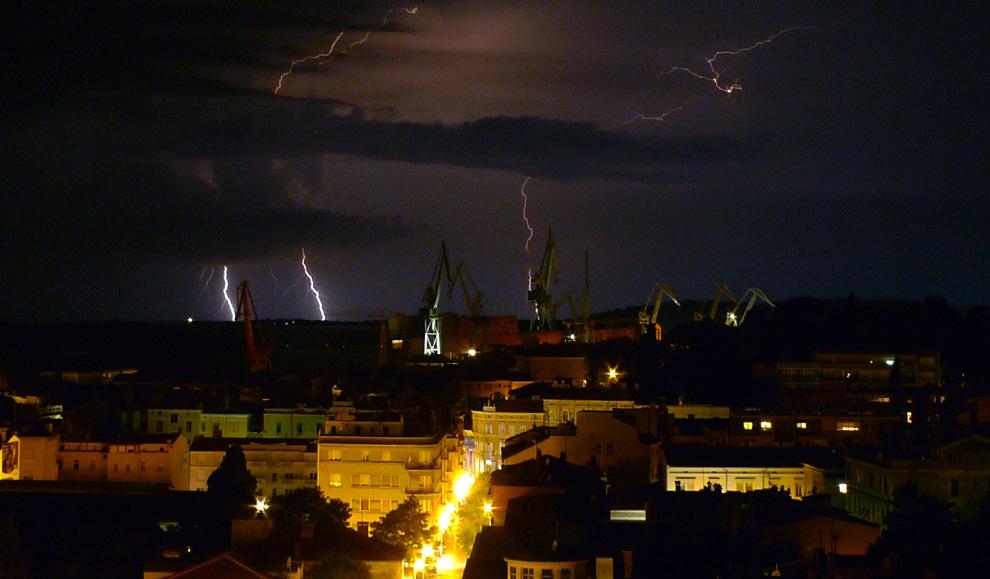 2) Вспышки молний освещают ночное небо во время летней грозы над хорватским адриатическим портом Пула 10 июля 2009. (REUTERS/Nikola Solic)