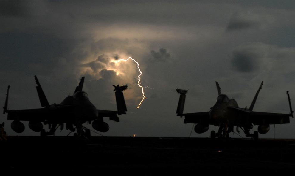 4) Молния между самолетами F/A-18C Hornet на полётной палубе авианосца «USS John C. Stennis» в Тихом океане 8 апреля 2009. (Mass Communication 2nd Class Elliott Fabrizio/U.S. Navy)