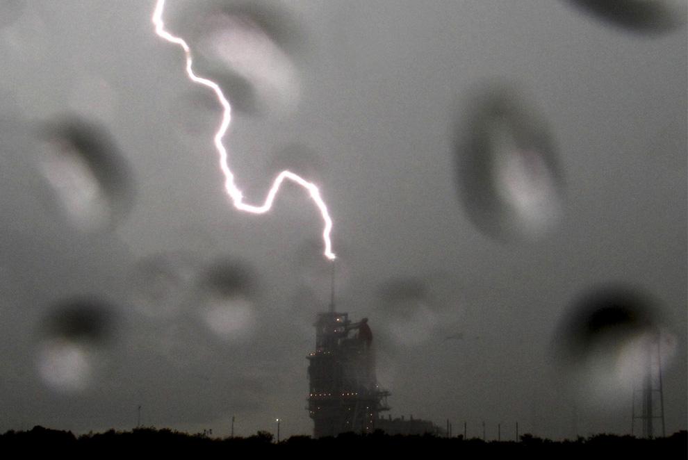 9) Молния ударяет в башню у космического шаттла Endeavour, который стоит на вершине стартовой площадке 39А во время грозы в Космическом центре Кеннеди на мысе Канаверал, штат Флорида 10 июля 2009. NASA отменили попытку запуска шаттла 11 июля 2009 для того, чтобы оценить возможный ущерб от удара молнии. (REUTERS/Gene Blevins)