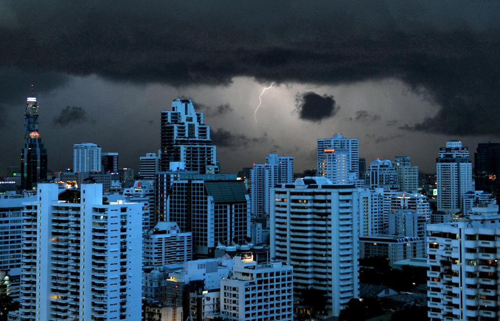 11) Молния освещает небо и отражается от поверхности зданий в Бангкоке 13 июня 2009. (NICOLAS ASFOURI/AFP/Getty Images)