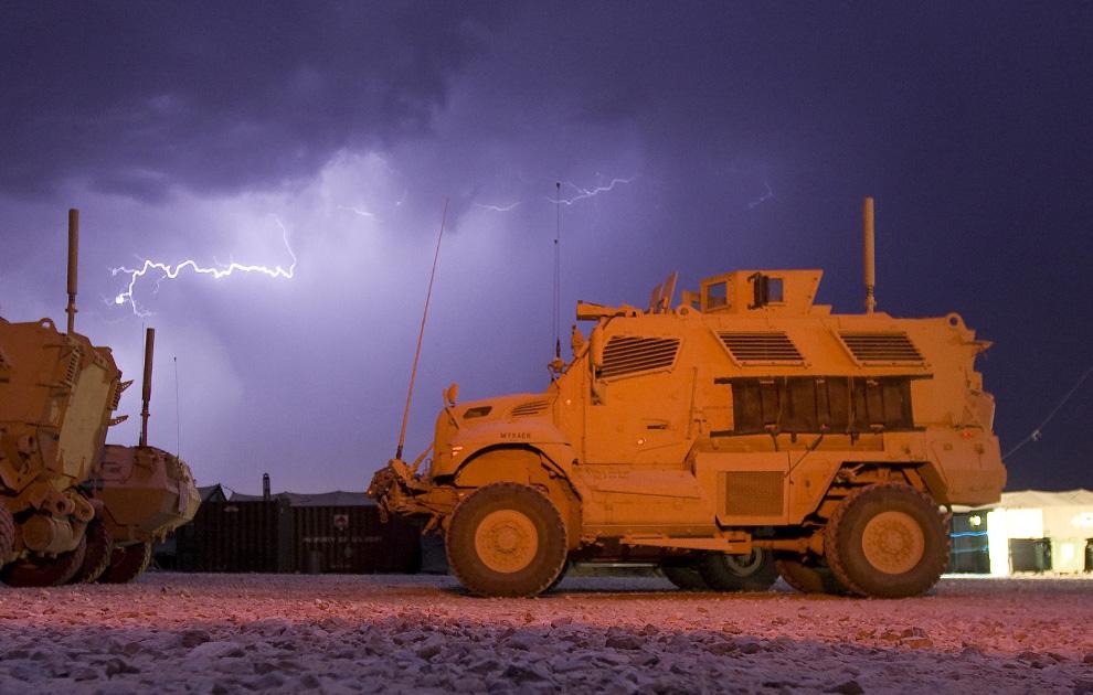 12) Молния во время грозы над бронемашиной с защитой от мин и внезапного нападения типа MRAP на территории американской оперативной базы в афганской провинции Логар 18 июля 2009. (REUTERS/Shamil Zhumatov)