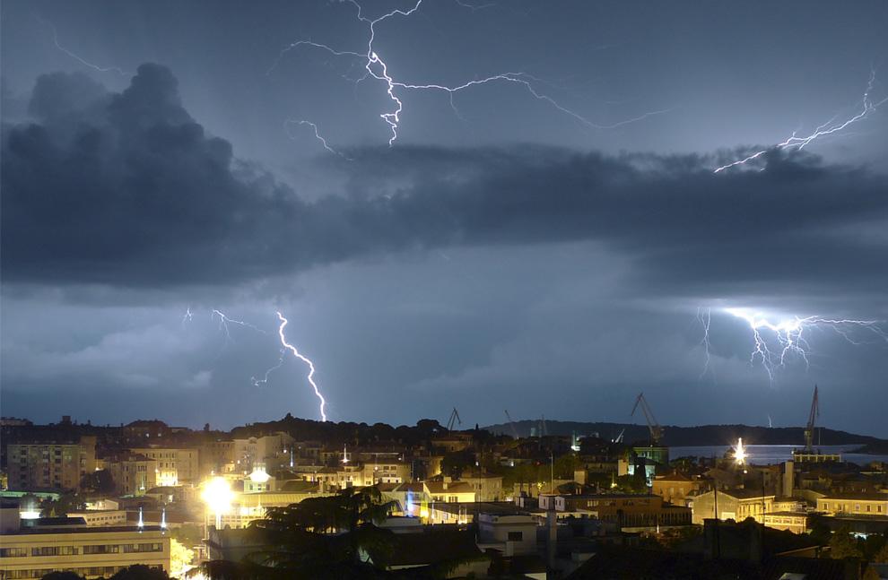13) Вспышки молний разрезают облака в небе над хорватским городом Пула, 10 июля 2009. (AP Photo/Darko Bandic)