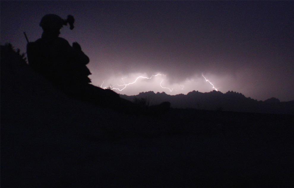 14) Американский морской пехотинец наблюдает за вспышками молний на горизонте во время операции по поиску талибов 25 марта 2009 году неподалеку от деревни Баква в отдаленных областях на юго-западе Афганистана. (John Moore/Getty Images)