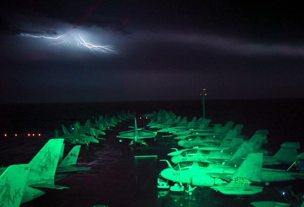 18) Снимок сделан в море на борту судна «Авраам Линкольн» 2 ноября 2002 года. Молния над горизонтом освещает полётную палубу. (Lt. Troy Wilcox/U.S. Navy)