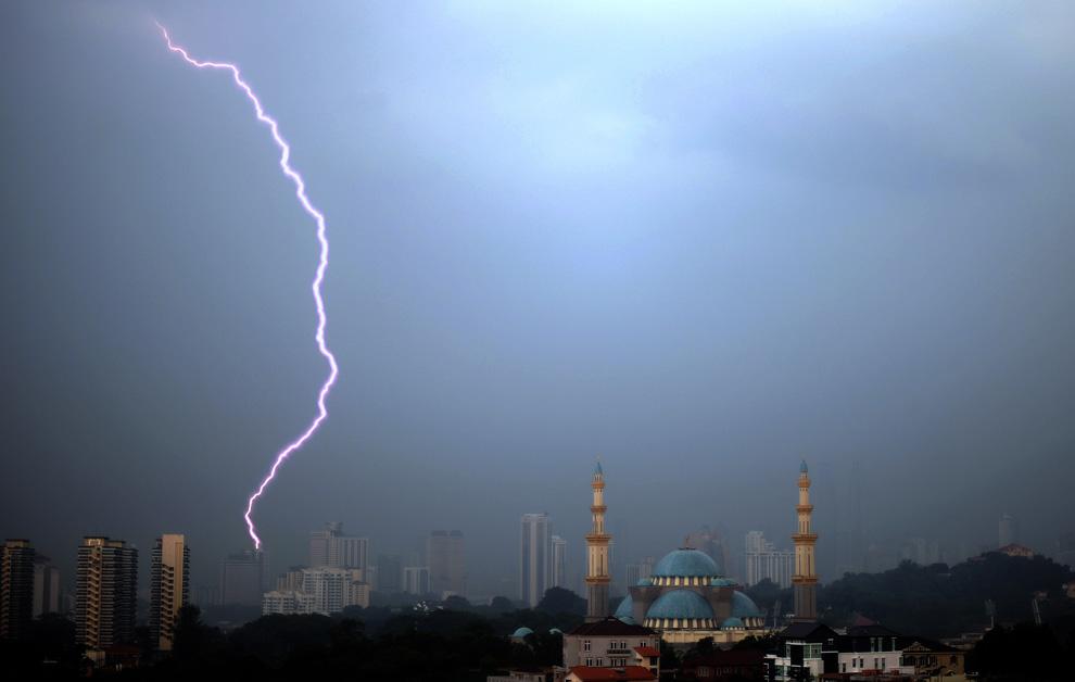 20) Вспышка молнии в небе над мечетью федеральной территории в Куала-Лумпуре, Малайзия, 24 июня 2009. (SAEED KHAN/AFP/Getty Images)