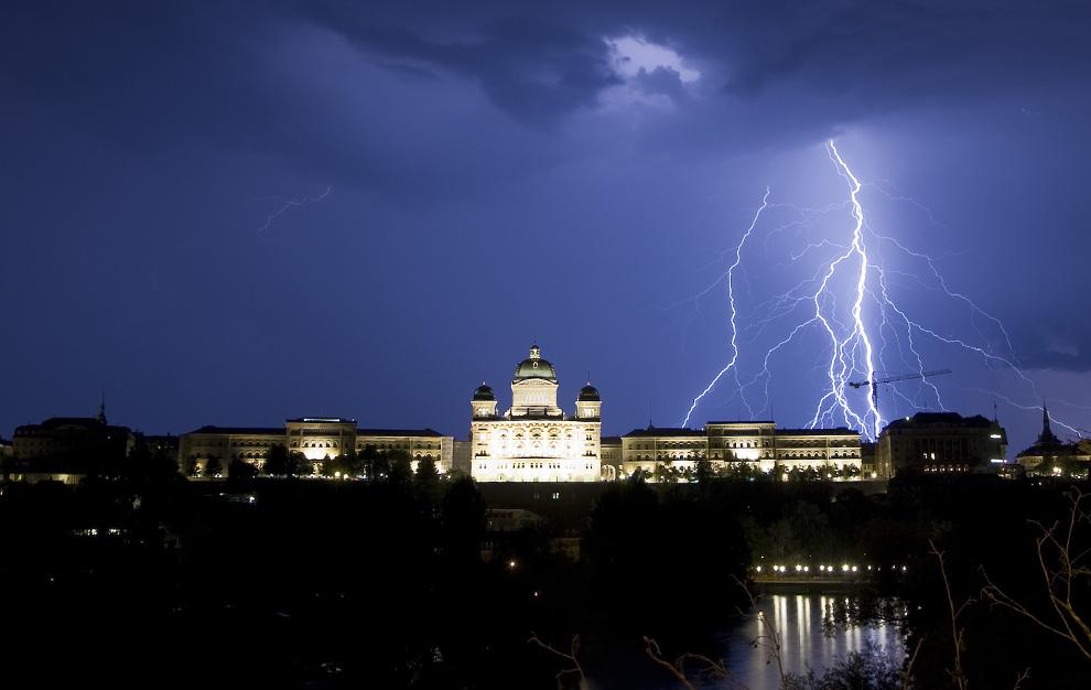 22) Молния освещает небо над Швейцарским Федеральным дворцом в Берне во время грозы 17 июля 2009. (REUTERS/Michael Buholzer)