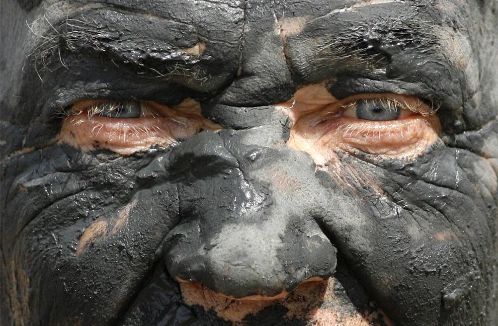 1) Мужчина измазанный в черной, богатой минералами грязи во время отдыха на берегах соленого озера Тус в Хакасии, которое расположено в 370 км к юго-западу от сибирского города Красноярска, 12 июля 2009. (REUTERS/Ilya Naymushin)