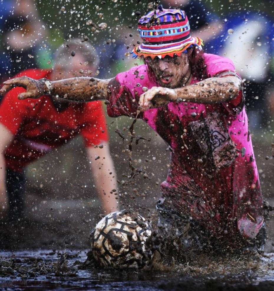 ) Игрок ведет борьбу за мяч во время Чемпионата Мира по болотному футболу 2009, проходящий в Хиринсалми, Финляндия, 17 июля 2009. Естественное болото превратилось в 22 игровых поля для 325 команд, таким образом, одновременно могли играть около 5000 игроков из Финляндии, России, Норвегии, Германии, Франции и Голландии. (REUTERS/Vesa Moilanen/Lehtikuva)