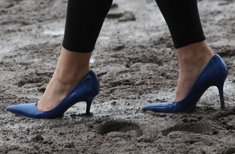 ) Журналистка и судья на скачках Джессика Пакетт проходит через грязный трек на высоких каблуках, Саффолк Даунс (Suffolk Downs), 24 июня 2009. «Честно говоря, я думаю о том, как бы ни упасть. Почему я надела туфли на высоком каблуке? Да потому что они подходят к моему платью». (Boston Globe Staff Photo)