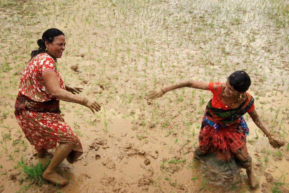 ) Непальские крестьянки кидаются друг в друга грязью на рисовом поле, расположенном на окраине Катманду, 29 июня 2009. Именно так каждый год крестьяне в Непале отмечают открытие сезона выращивания риса. Этот день носит название «Национальный день грязи». (PRAKASH MATHEMA/AFP/Getty Images)