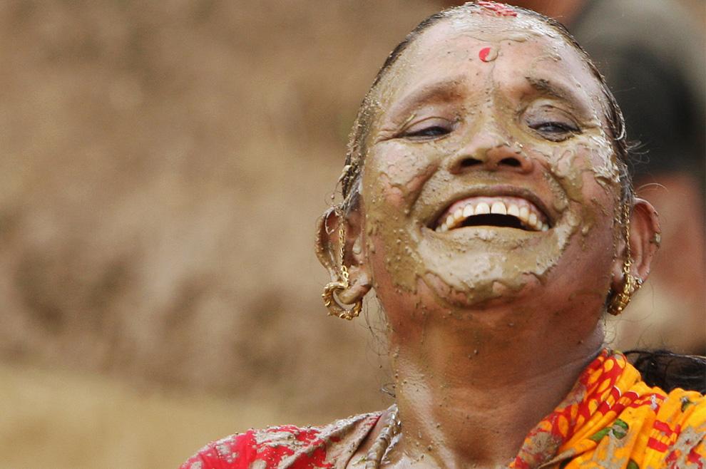) Женщина перемазана грязью во время «Национального дня грязи» на окраине Катманду, 29 июня 2009. Таким образом, крестьяне отмечали начало сезона выращивания риса. (PRAKASH MATHEMA/AFP/Getty Images)