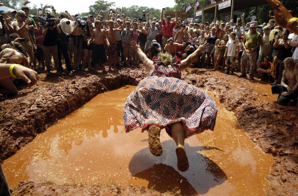 """) Барбара Бейли «Королева деревенщин» демонстрирует высший пилотаж по падению животом в грязь. Снимок сделан на """"Играх деревенщин"""" 11 июля 2009 года в Восточном Дублине, штат Джорджия. Бейли несколько лет в 1990-е побеждала в этом соревновании. Впервые проведенные в 1996 году в качестве пародии на летние Олимпийские игры, которые состоялись в Атланте, """"Игры деревенщин"""" включают в себя такие соревнования, как прыжки в грязь, метание туалетных стульчаков,  драки за свиные ножки и так далее. (Stephen Morton/Getty Images)"""