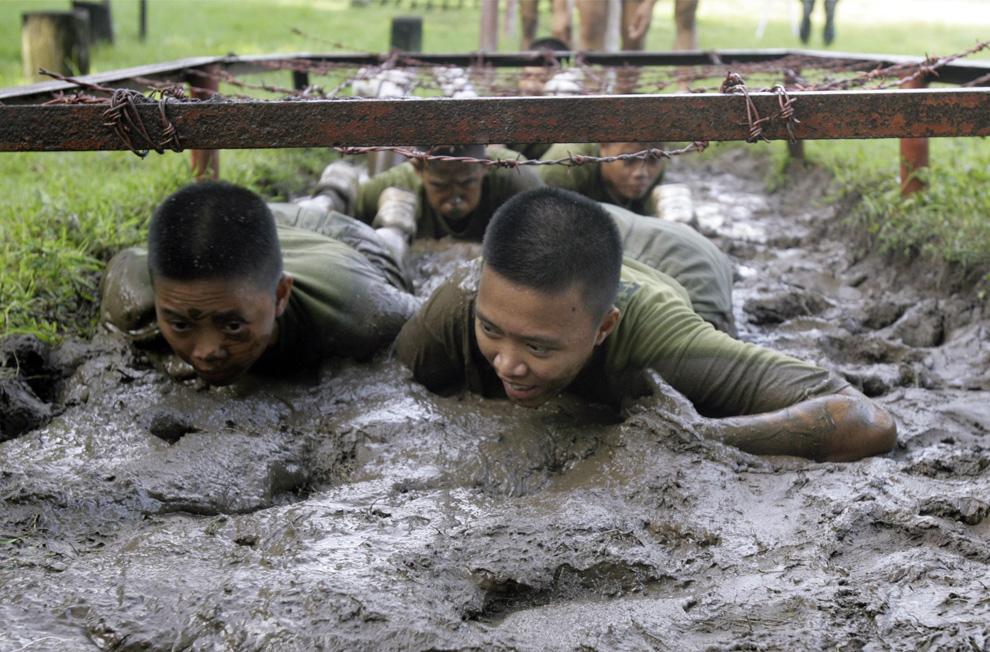 """) Женщины-военнослужащие ползут в грязи во время учений морской пехоты на военной базе в Кавите-Сити (Cavite city), на юге Манилы, 8 июля 2009. Теперь женщин набирают и в филиппинскую морскую пехоту, которая на фронтовой линии южно-филиппинского острова Минданао сражается с боевиками-исламистами. Именно на этом острове итальянский инженер Красного Креста был захвачен мусульманскими мятежниками и провел в плену около 6 месяцев. Люди, захватившие итальянца, связаны с индонезийской религиозной экстремистской группировкой """"Джемаа Исламия"""" (Jemaah Islamiah). (REUTERS/Romeo Ranoco)"""