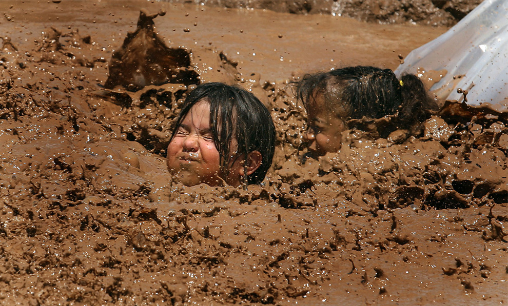 ) 5-летние Эйша Ривьера и Жасмин Майлз нырнули с головой в грязь после того как скатились с горки в огромное грязевое озеро во время 7-го ежегодного праздника «Monsoon Madness» в Квин Крик, Аризона, в субботу, 11 июля 2009. (AP Photo/East Valley Tribune, Darryl Webb)