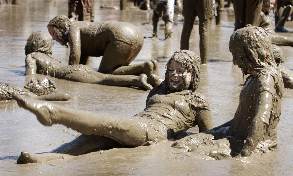 ) 13-летняя Келли Йоком (в центре), из города Эдфорд, штат Мичиган, и ее подруга, 9-летняя Стефани Янссена (справа), из Редфорда, играют вместе с сотнями других детей в гигантском грязевом озере на ежегодном празднике День Грязи 7 июля 2009 года в Вестленд, Мичиган. (Bill Pugliano/Getty Images)