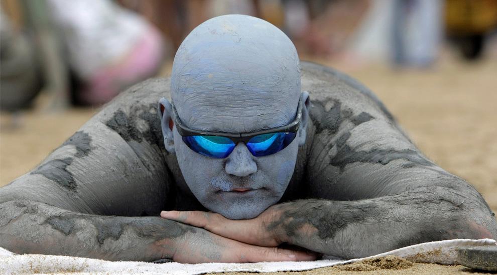 ) Британец Джастин Беттеридж загорает на пляже Тэчхон во время Грязевого фестиваля в Порене. (AP Photo/ Lee Jin-man)