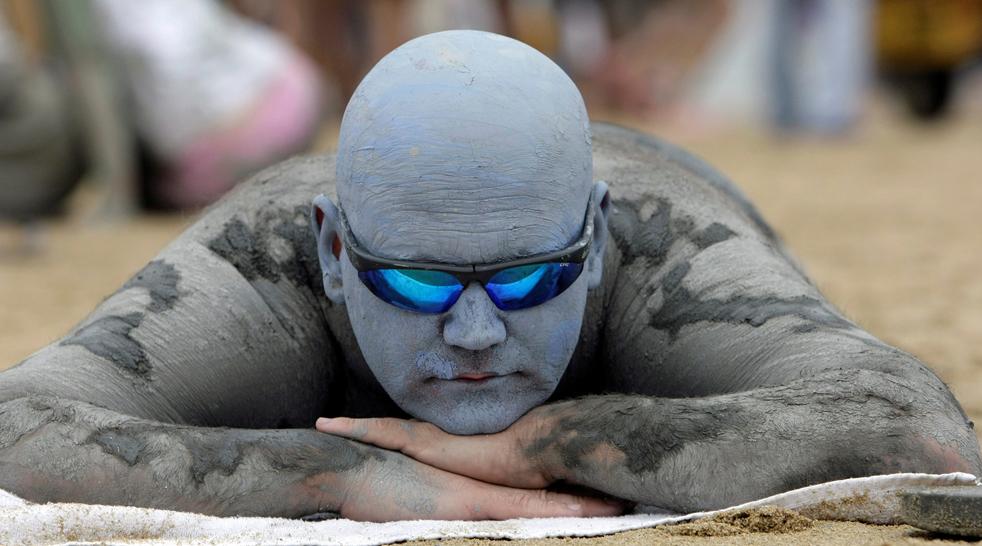 Британец Джастин Беттеридж загорает на пляже Тэчхон во время Грязевого фестиваля в Порене. (AP Photo/  Lee Jin-man)