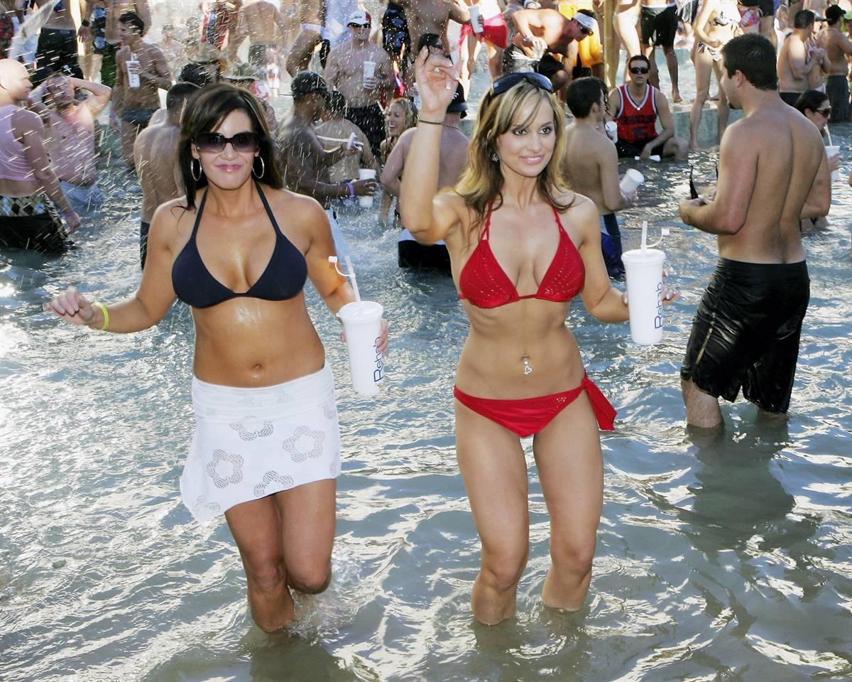 19) Дина Буэлл, слева и Карла Джордано, из Калифорнии, танцуют у бассейна в отеля-казино «Хард Рок Отель» во время еженедельной вечеринке в бассейне Реабилитация, в 2005 году в Лас-Вегасе. (Ethan Miller/Getty Images)
