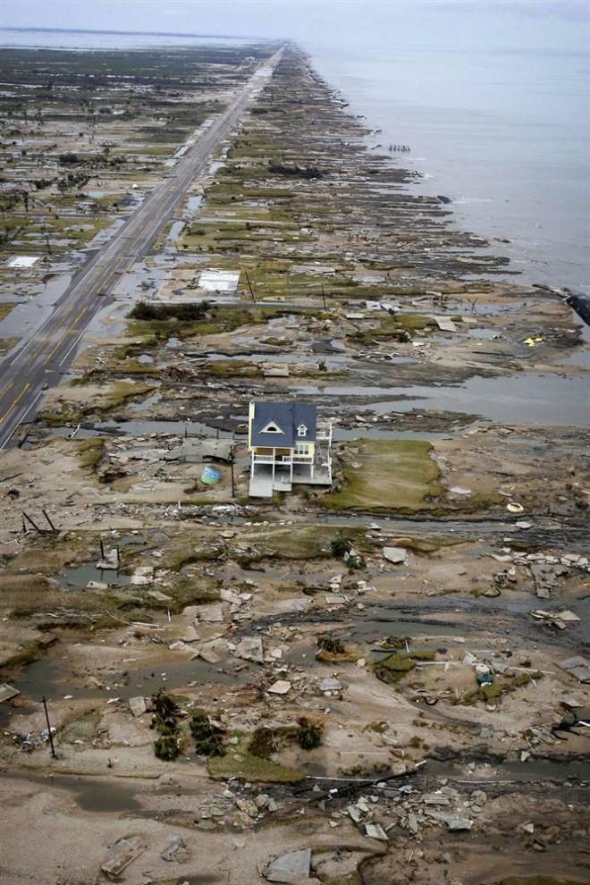 2) 14 сентября 2008, спустя день после того, как ураган Айк подошел к побережью, уцелевшим остался только один дом, стоящий среди развалин разрушенных домов в городе Джилкрист, Техас. (David J. Phillip/Getty Images)