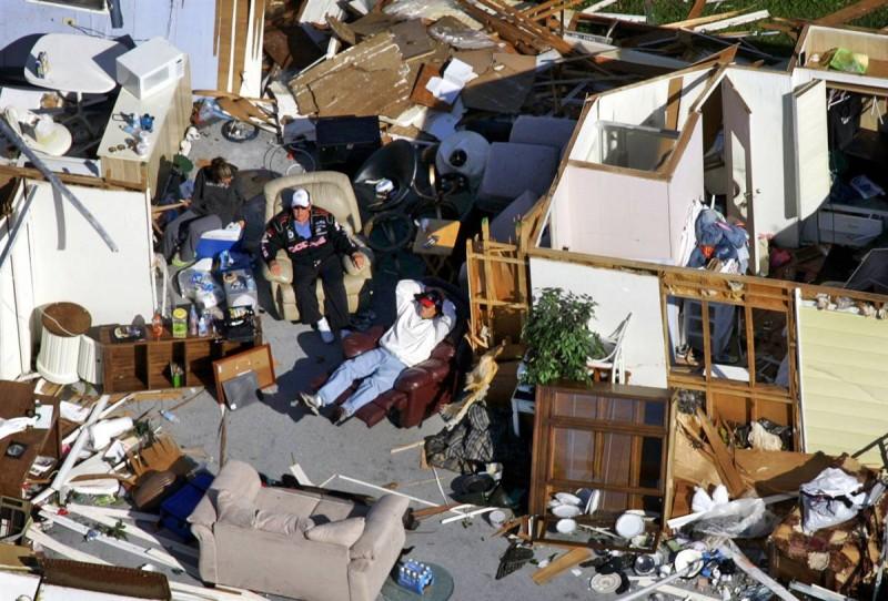 4) Мужчины сидят в разрушенном передвижном домике в Форт-Лодердейле, Филадельфия, 25 октября 2005, после урагана Вилма, пронесшегося через весь штат приблизительно за семь часов. Убытки, причиненные ураганом, составили $21,5 миллиарда. (Wilfredo Lee/AP)