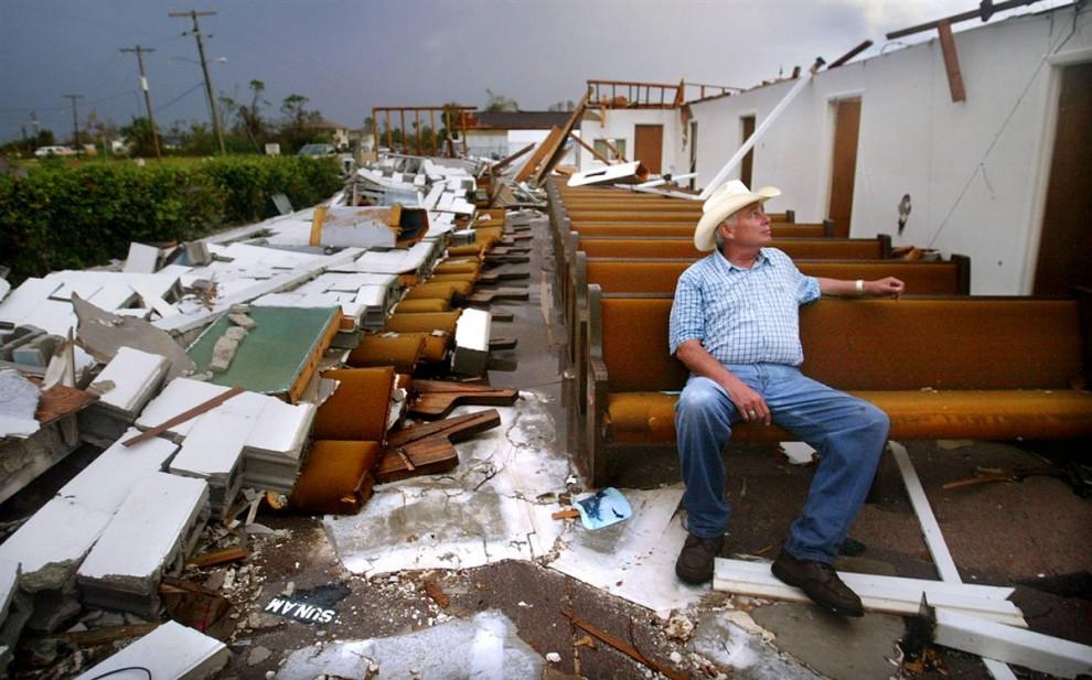 12) Доброволец Бадди Шипп в разрушенной Церкви Христа Пис-Ривер в Пунта Горда (Punta Gorda), Флорида, 22 августа 2004. Крышу церкви сорвало ураганом Чарли, но верующие поклялись ее восстановить. Материальный ущерб от Чарли достиг $16,3 миллиардов. (Mario Tama/Getty Images)