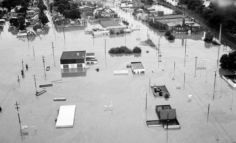 22) Наводнения, вызванные дождем от урагана Агнес, затопляют дома в Потстауне, Пенсильвания, 23 июня 1972. Агнес стала причиной 122 смертей. (AP)