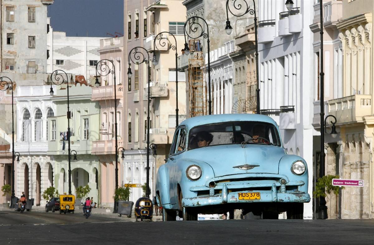 """Кубинцы едут на старом автомобиле по набережной """"Малекон"""" в Гаване. ЮНЕСКО внесло Старую Гавану и ее фортификации в Список всемирного наследия в 1982 году. Хотя Гавана расширилась, и ее население составляет более 2-х млн. человек, ее старый центр сохраняет интересную смесь памятников в стиле барокко и неоклассицизма и однородных ансамблей частных домов с аркадами, балконами, воротами из кованого железа и внутренними двориками. (Javier Galeano/AP)"""