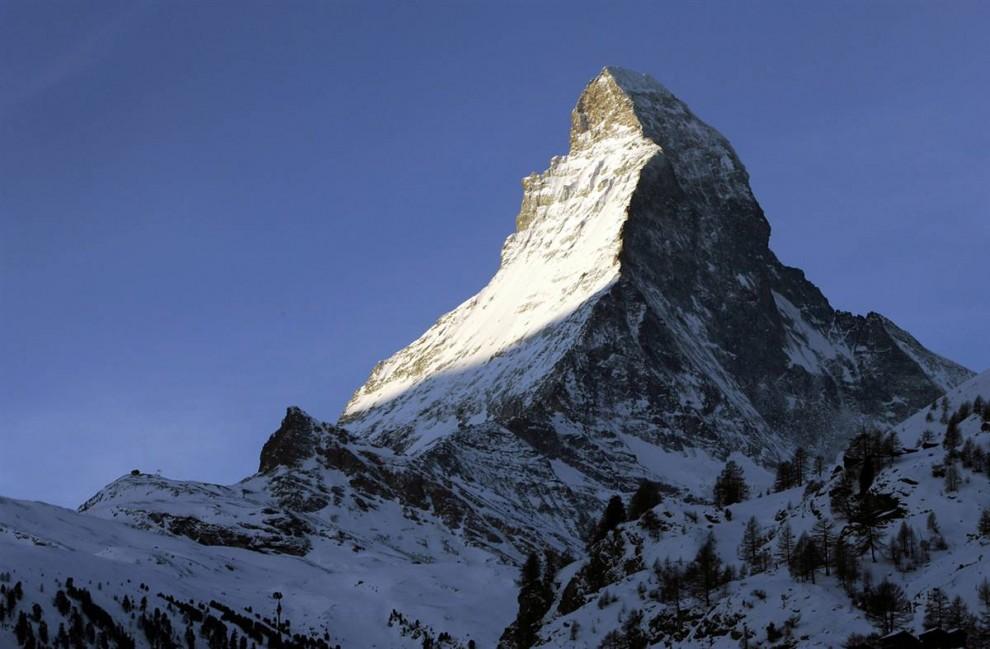 ) Гора Маттерхорн на границе Италии и Швейцарии не самая высокая (14,690 футов), но наверное самая впечатляющая. К ее вершине сходятся четыре треугольные грани и она принимает пирамидальную форму. (Olivier Maire / AP)