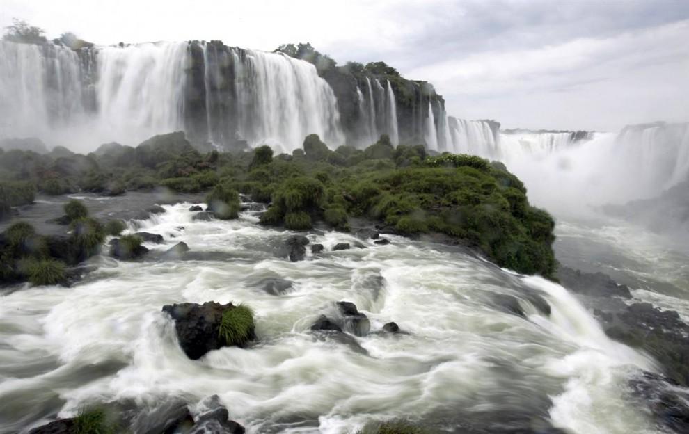) Расположенный на границы Бразилии и Аргентины водопад Игуасу является одним из самых протяженных каскадов водопадов в мире. Его длина составляет около 2 миль. «Глотка дъявола» (справа) - самый высокий среди водопадов. Игуасу с двух сторон окружен Национальными парками с тропическими джунглями. (Juan Mabromata / AFP - Getty Images)
