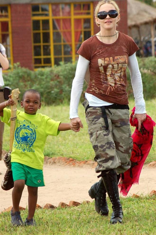 4) Мадонна и ее приемный сын Дэвид Банда во время посещения финансируемого ее фондом Raising Malawi детского центра Мфандула в Лилонгве, Малави. Певица усыновила Дэвида в 2009 году, а сейчас идет процесс по удочерению малавийской девочки. (Amos Gumulira/AFP - Getty Images)