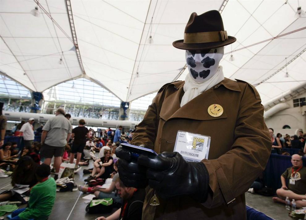 """32) Шон Хили, одетый в костюм Роршаха (Rorschach), персонажа из известного комикса """"Хранители"""" (Watchmen), воспользовался свободной минуткой пока стоит в очереди на фестиваль Comic-Con в сан-Диего и пишет сообщение. (Denis Poroy/AP)"""