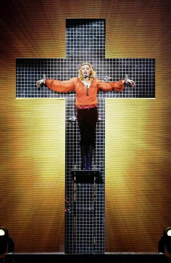 """13) Мадонна выступает на Wembley Arena в рамках мирового турне """"Confessions"""" («Религии»), 2006. Своим шоу Мадонна снова вызвала множество споров, используя во время выступления религиозные символы, такие как кресты, распятие, терновый венец. (Getty Images)"""