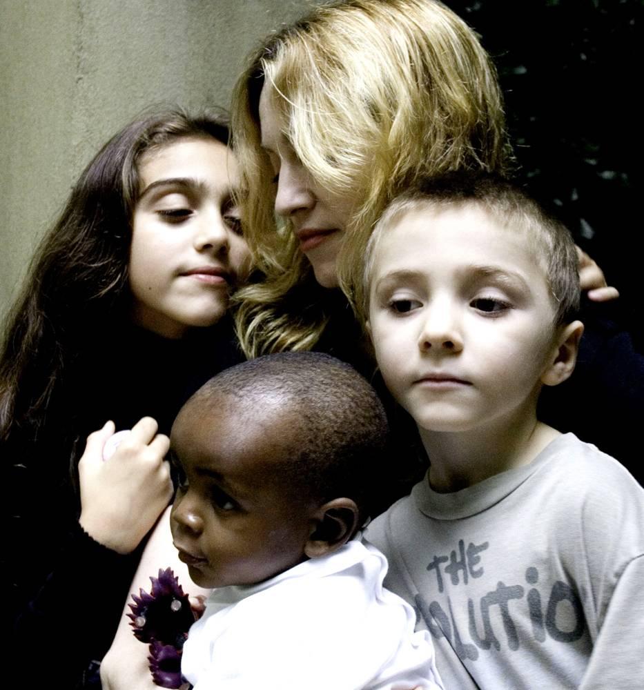 """10) Мадонна обнимает своих детей: 9-летнюю дочь Лурдес (слева), 6-летнего сына Рокко и годовалого Дэвида Банду, которого они вместе с Гаем Ричем усыновили. В интервью 25 октября 2006 года, которое Мадонна дала """"The Oprah Winfrey Show"""", она сказала, что Дэвид здоров, живет и подрастает в ее доме в Лондоне. (Shavawn Rissman/AP)"""