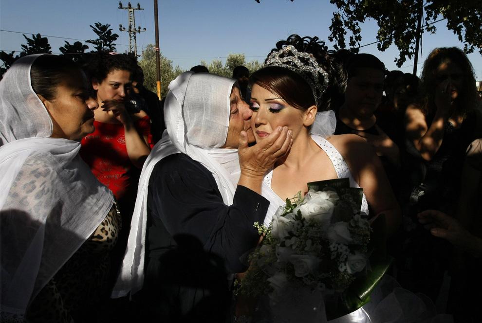 3) Одна из родственниц Арин Сафади целует ее на прощанье перед тем, как Арин покинет свой дом навсегда, чтобы жить со своим мужем в Сирии. 25 сентября 2008. (MENAHEM KAHANA/AFP/Getty Images)
