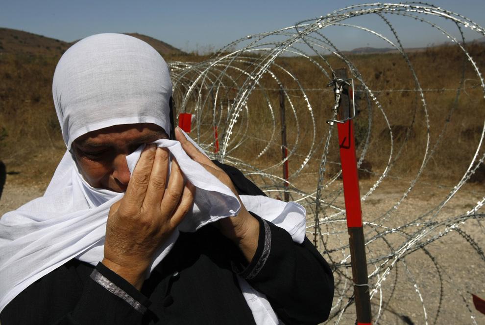 8) Одна из родственниц Арин Сафади плачет, стоя на границе между Израилем и Сирийской 25 сентября 2008. (MENAHEM KAHANA/AFP/Getty Images)