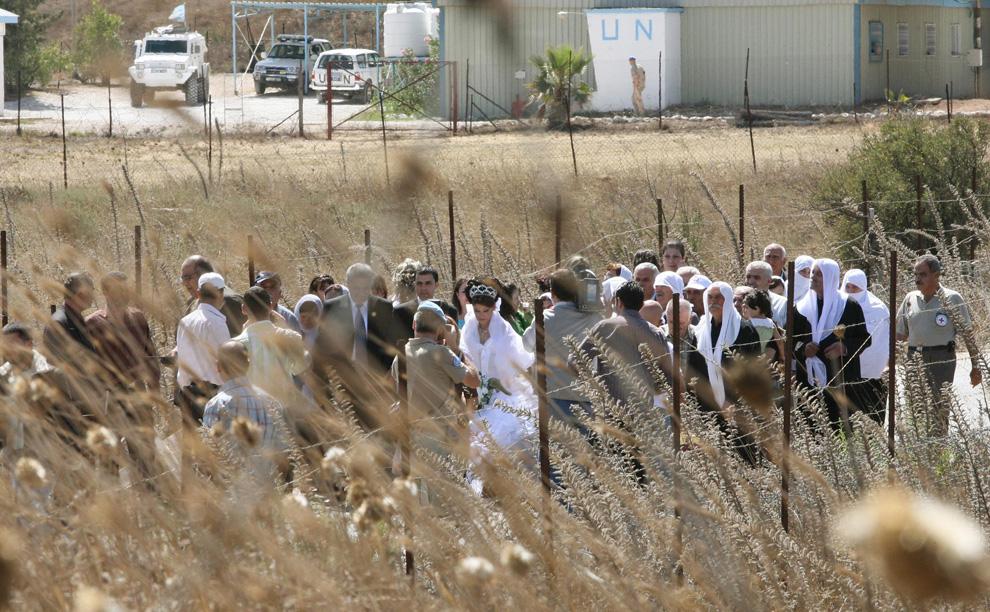 9) Арин Сафади со своим мужем, Рабиа Сафади (справа от нее) проходит через контрольно-пропускной пункт на сирийско-израильской границе, 25 сентября 2008. (REUTERS/Khaled al-Hariri)