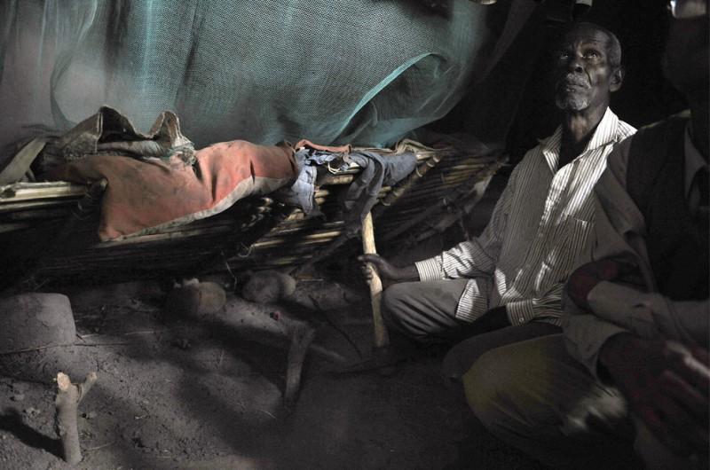2) 76-летний Мабула сидит на корточках в спальне с земляным полом, возле могилы своей внучки, пятилетней Мариам Эммануэль, маленькой альбиноски, которая была убита и расчленена в соседней комнате в феврале 2008 года. Девочку похоронили прямо в хижине, чтобы охотники за частями тел альбиносов не растащили ее кости. Снимок сделан 25 января 2009 года в одной из деревень близ Мванзе. (TONY KARUMBA/AFP/Getty Images)