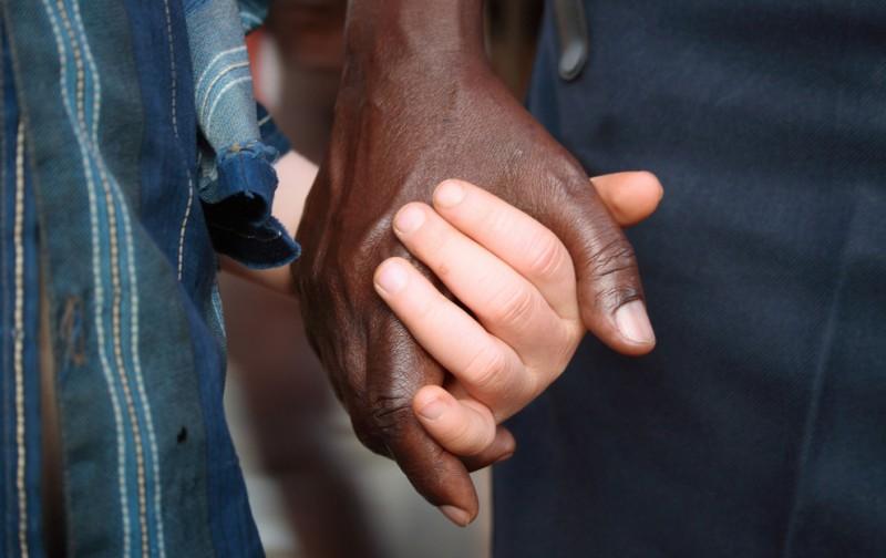 7) Доброволец из Танзанийского Общества Красного Креста (TRCS) держит за руку малыша-альбиноса на пикнике, организованном в TRCS в государственной школе для инвалидов в Кабанге, на западе страны близ города Кигому на озере Танганьика 5 июня 2009. (REUTERS/Alex Wynter/IFRC/Handout)