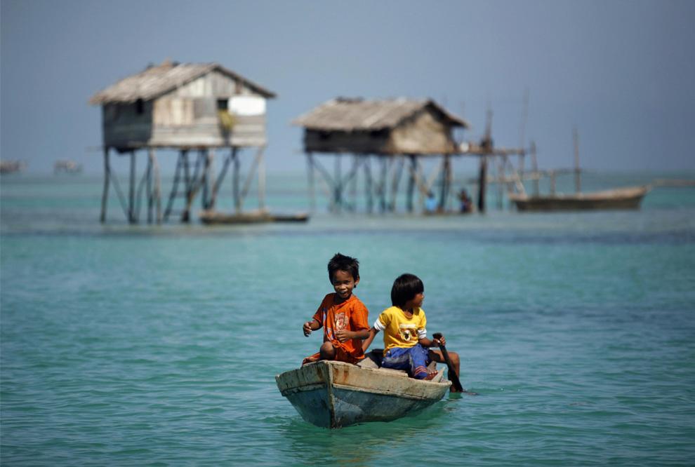 10) Мальчики из племени морских цыган гребут на лодке неподалеку от своего дома в море Сулавеси в малазийском штате Сабах на Борнео. Снимок сделан 17 февраля 2009. (REUTERS/Bazuki Muhammad)