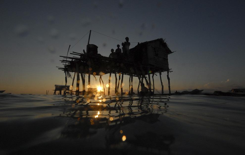 9) Семейство морских цыган собралось на палубе своей хижины, которая расположена в море Сулавеси в малазийском штате Сабах на Борнео. Снимок сделан 17 февраля 2009. (REUTERS/Bazuki Muhammad)