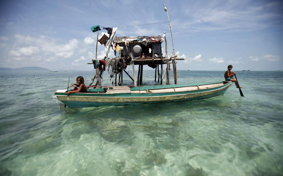 4) Дети сидят на своих лодках у хижины их семьи в малазийском штате Сабах на Борнео 17 февраля 2009. (REUTERS/Bazuki Muhammad (MALAYSIA)