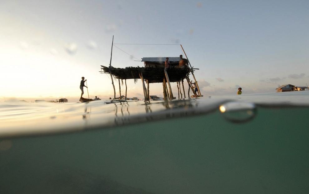 3) Мальчик из племени морских цыган гребет на лодке через жилой район в море Сулавеси, Малайзия, 17 февраля 2009. (REUTERS/Bazuki Muhammad (MALAYSIA)