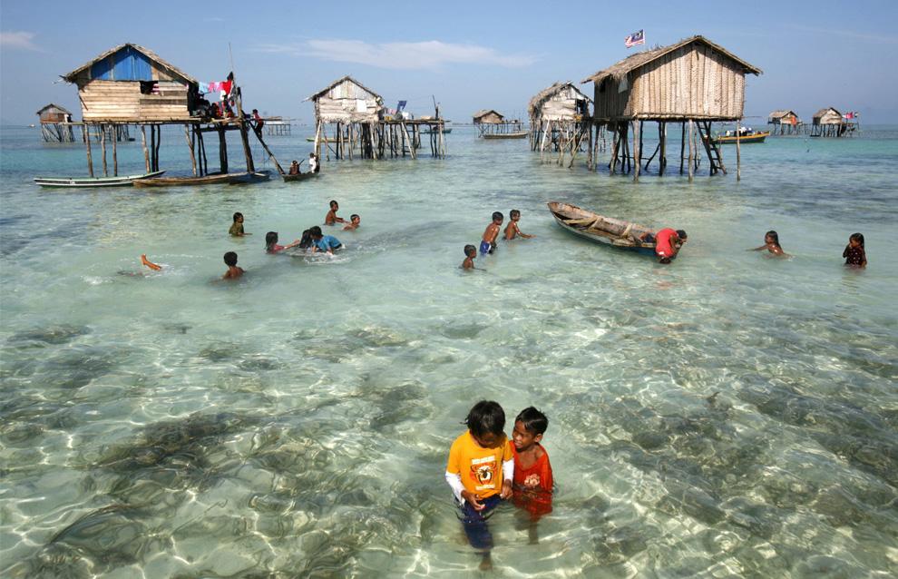 2) Маленькие морские цыгане играют в воде среди домов в море Сулавеси, 17 февраля 2009. (REUTERS/Bazuki Muhammad (MALAYSIA)