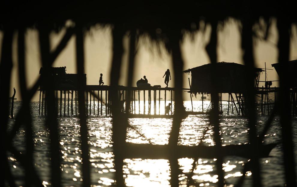 1) Семья собралась на палубе хижины на закате 17 февраля 2009. (REUTERS/Bazuki Muhammad (MALAYSIA)