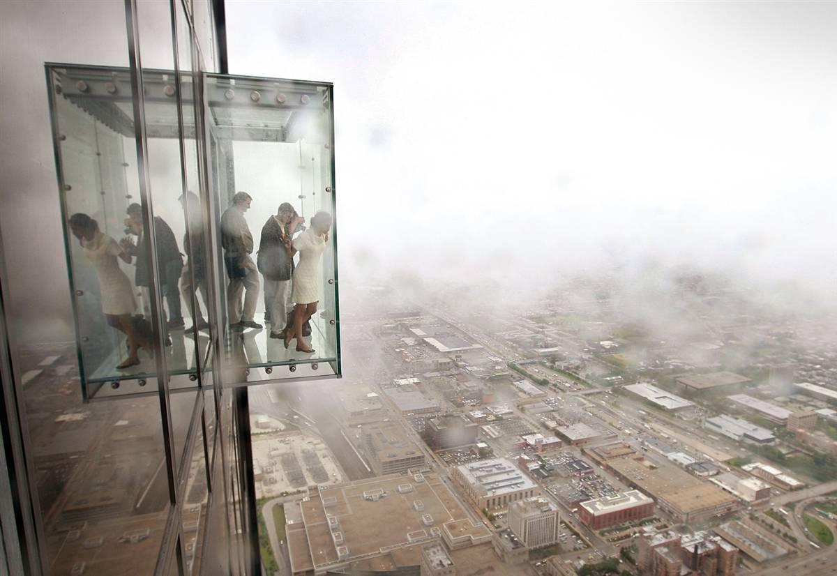 1) Посетители любуются видом из The Ledge, новый смотровой площадки на самом высоком небоскребе США, Сирс Тауэр в Чикаго. Она находится на 103 этаже (около 412 метров) и открыта для посещения публики. (Scott Olson/Getty Images)