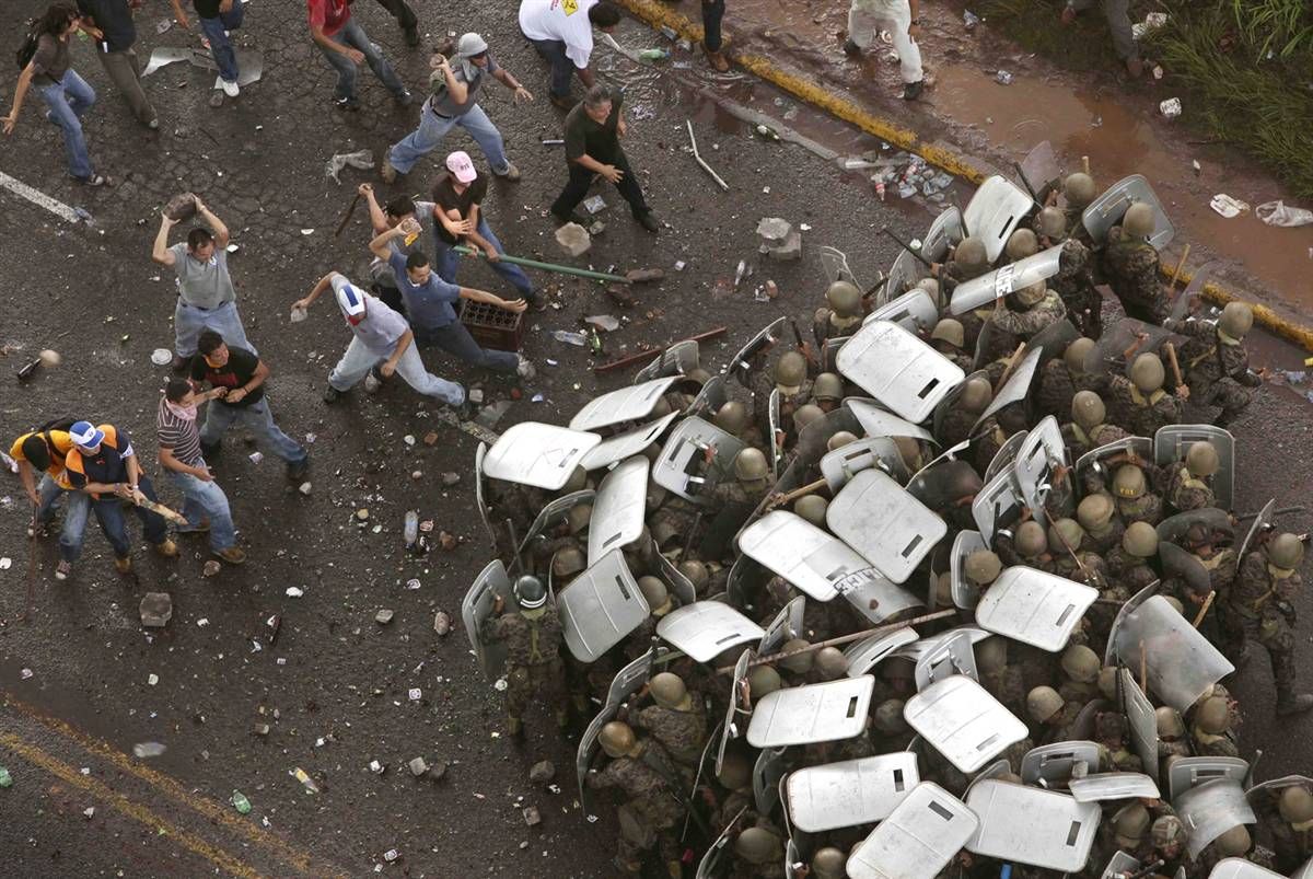 2) Сторонники свергнутого президента Гондураса Мануэля Селайи во время столкновения с солдатами возле резиденции президента в Тегусигальпе 29 июня. Полиция применила слезоточивый газ, чтобы сдержать напор тысячной толпы. Мировые лидеры от Барака Обамы до Уго Чавеса призвали Гондурас отменить переворот, во время которого был свергнут Селайя. (Esteban Felix/AP)