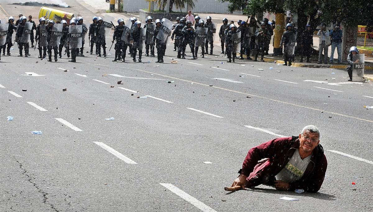3) Демонстрант на улице во время столкновений между сторонниками свергнутого президента Гондураса Мануэля Селайи, солдат и полицейских в Тегусигальпе 29 июня. Исполняющий обязанности президента Роберт Мичелетти ввел общенациональный 48-часовой комендантский час, после того, как армия свергла Селайю, избранного 28 июня. (Orlando Sierra/AFP - Getty Images)