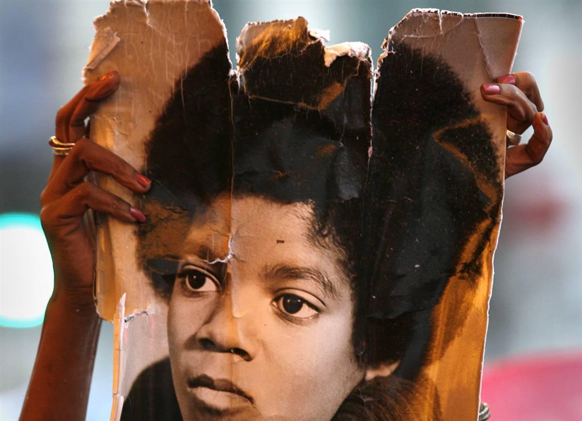 """6) Один из фанатов держит старое фото Майкла Джексона во время его поминок в театре """"Аполло"""" в Нью-Йорке 30 июня. В театре собрались около 600 фанатов, для того чтобы отдать дань уважения Джексону, послушать его музыку смиксованную нью-йоркскими диджеями и посмотреть видео-трибьют покойной поп-звезды. (Lucas Jackson/Reuters)"""