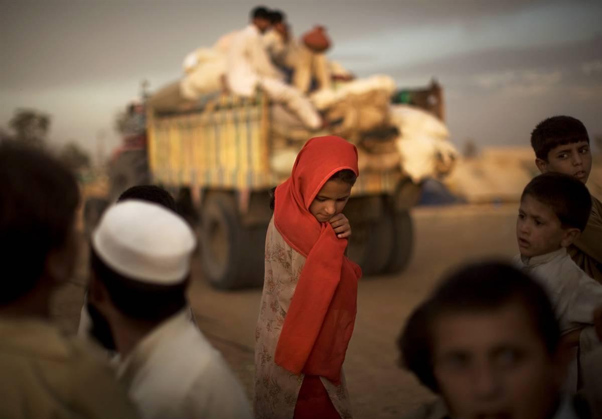 8) Пакистанская девочка-беженка,  временно проживающая в районе Сваби смотрит на то, как ее семья готовится к возвращению на родину 29 июня. Правительство призывает пакистанцев из региона Бунер вернуться домой, однако запланированное перемещение беженцев откладывается из-за взрыва бомбы в этом регионе. (Daniel Berehulak/Getty Images)